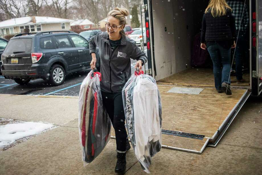 Janine Bensch, clothing coordinator for Midland's Open Door, unloads items from a trailer as Open Door sets up a new space for their clothing assistance program Thursday at Emmanuel Baptist Church. (Katy Kildee/kkildee@mdn.net)