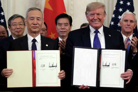 President Donald Trump signs a trade agreement with Chinese Vice Premier Liu He, in the East Room of the White House, Jan. 15, 2020, in Washington.