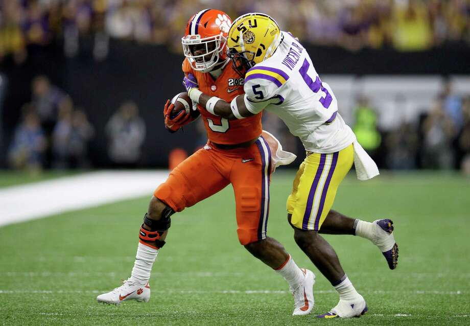NEW ORLEANS, LOUISIANA - JANUARY 13: Travis Etienne #9 of the Clemson Tigers runs with the ball against Kary Vincent Jr. #5 of the LSU Tigers during the first quarter in the College Football Playoff National Championship game at Mercedes Benz Superdome on January 13, 2020 in New Orleans, Louisiana. (Photo by Chris Graythen/Getty Images) Photo: Chris Graythen, Staff / Getty Images / 2020 Getty Images