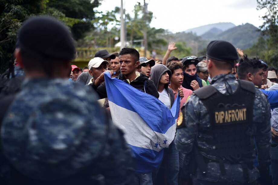 Honduran migrants stand in front of a line of Guatemalan police officers at the Agua Caliente border crossing. Photo: Johan Ordonez / AFP / Getty Images