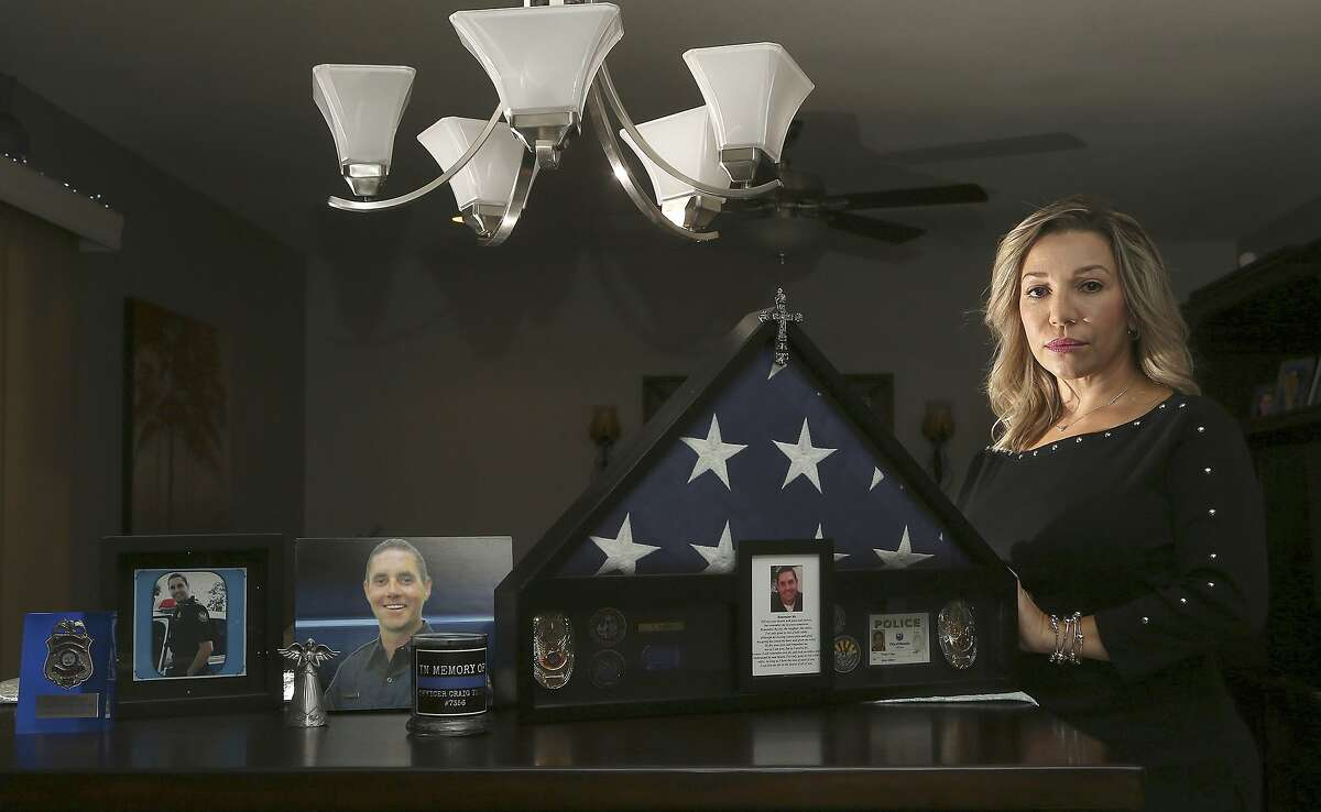 Rebecca Tiger, a former Phoenix police officer, is the widow of Craig Tiger, a Phoenix police officer who committed suicide a few years ago following a fatal shooting he was involved in, shown at her home Monday, July 1, 2019, in Scottsdale, Ariz. Officer Craig Tiger suffered from post-traumatic stress disorder after fatally shooting a man while on duty back in 2012, and took his own life two years later. (AP Photo/Ross D. Franklin)