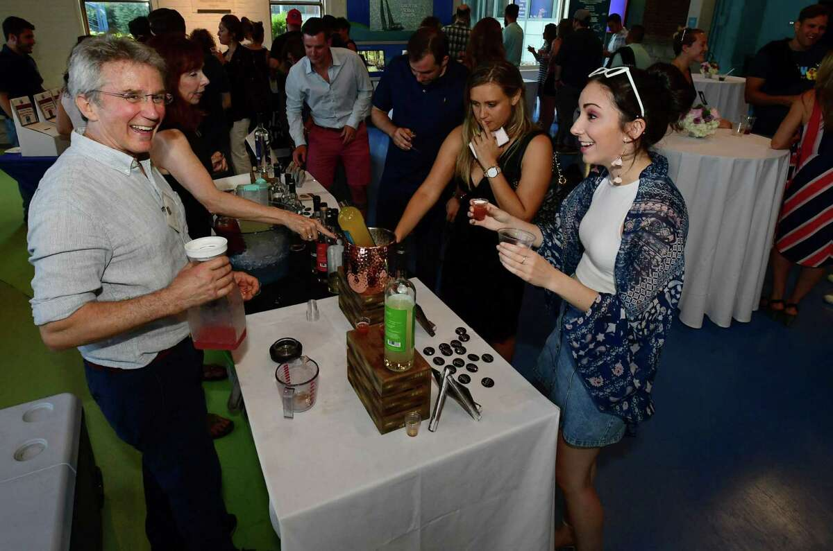 """Asylum Distillery's Robert Schulten pours for Stratford resident Amy Craw during """"Maritime with a Twist"""" in June at the Maritime Aquarium in Norwalk. Connecticut distillers stand to benefit when the state's new craft café permit legislation goes into effect July 1, paving the way for distilleries to serve drinks at their facilities."""