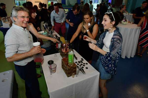 "Asylum Distillery's Robert Schulten pours for Stratford resident Amy Craw during ""Maritime with a Twist"" in June at the Maritime Aquarium in Norwalk. Connecticut distillers stand to benefit when the state's new craft café permit legislation goes into effect July 1, paving the way for distilleries to serve drinks at their facilities."