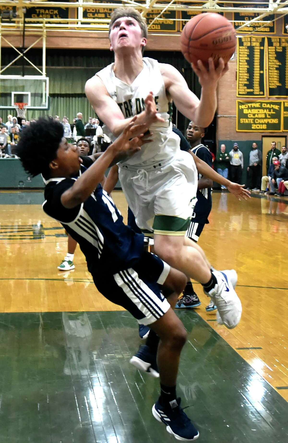 Hillhouse's Khalel Francis, left, and Notre Dame-West Haven's Zach Laput collide underneath the basket during a game earlier this month.