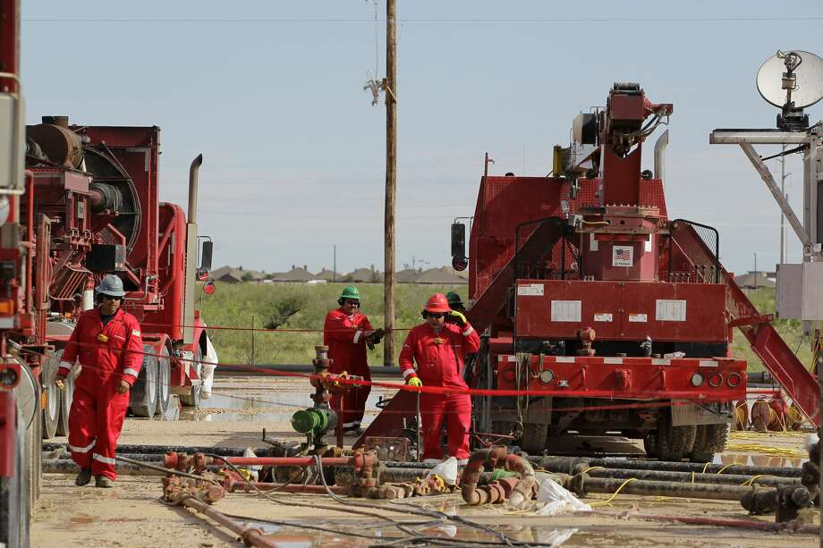 """Halliburton's employees work at a three wellhead fracking site Monday, June 26, 2017, in Midland. As operators seek ways to mitigate the """"frac hits"""" between parent and child wells, TenEx Technologies has devised a chemical solution that pressurizes the reservoir, keeping hydraulic fracturing sands and solutions from the newer wells away from the older wells. Photo: Steve Gonzales/Houston Chronicle"""