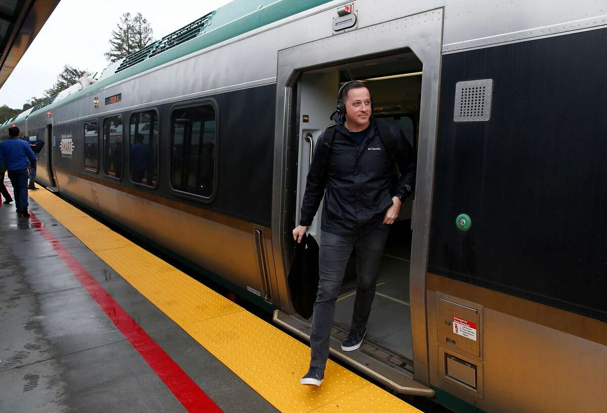 A passenger emerges from a SMART train after it arrives at the new station in Larkspur, Calif. on Friday, Dec. 13, 2019. A five minute walk links commuters arriving at the southernmost station in the SMART train system to the Golden Gate Ferry terminal across the street.