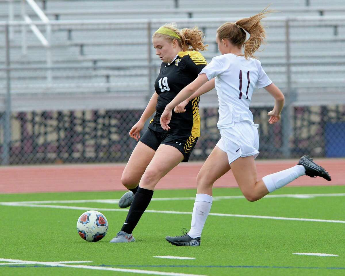 Sara Price (19) of St. Agnes passes a ball while challenged by Aubrey Crist (11) of CyFair during the first half of a high school soccer game between the CyFair Bobcats and the St. Agnes Tigers in the I-10 Shootout on Thursday, January 9, 2020 at Cinco Ranch High School, Katy, TX.