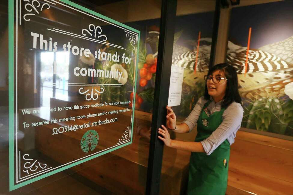 In this Wednesday, Jan. 15, 2020, photo, Belith Ariza, a barista trainer at Starbucks, opens the doors to the community meeting space at a local Starbucks Community Store, in Phoenix. The Seattle-based company plans to open or remodel 85 stores by 2025 in rural and urban communities across the U.S. That will bring to 100 the total number of community stores Starbucks has opened since it announced the program in 2015. (AP Photo/Ross D. Franklin)