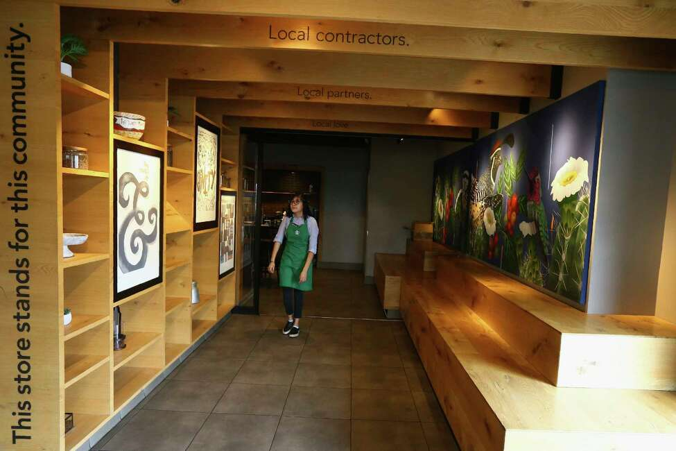 In this Wednesday, Jan. 15, 2020, photo, Belith Ariza, a barista trainer at Starbucks, walks back to the main store from the community meeting space at a local Starbucks Community Store, in Phoenix. The Seattle-based company plans to open or remodel 85 stores by 2025 in rural and urban communities across the U.S. (AP Photo/Ross D. Franklin)