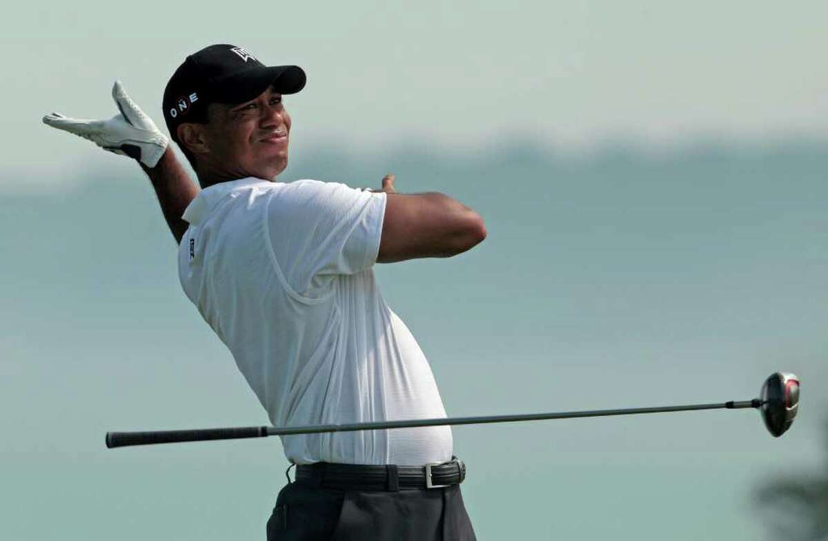 Tiger Woods drops his club as he drives on the fifth hole during the first round of the PGA Championship golf tournament Thursday, Aug. 12, 2010, at Whistling Straits in Haven, Wis. (AP Photo/Charlie Riedel)