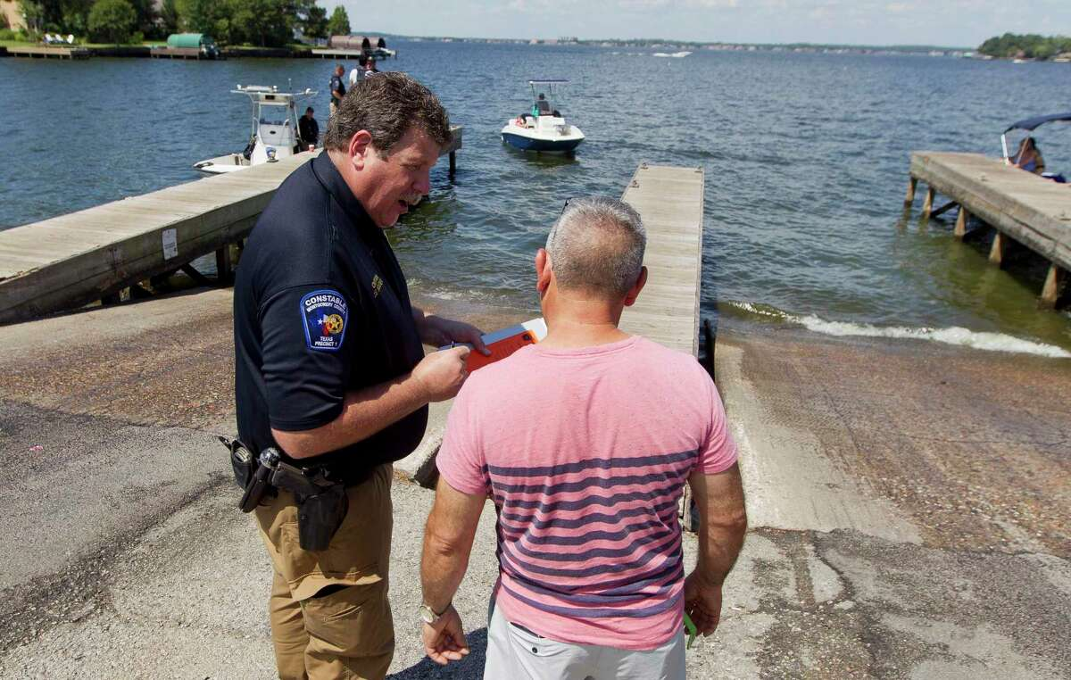 Capt. Joe Sclider, with the Precinct 1 Constable's Office, works with boaters to administers voluntary safety checks before enjoying Lake Conroe on Labor Day, Monday, Sept. 2, 2019, in Conroe.