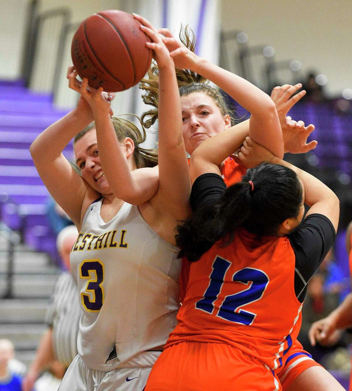Westhill's Peyton Hackett (3) fights for the rebound with Danbury's Chloe Perreault (3) and Viviana Flores (12) in the first half of an FCIAC girls basketball game in Stamford, Conn. on Jan. 16, 2020. Danbury defeated Westhill 60-35.
