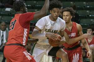 Midland College's Elijah Scranton drives to the basket between Howard College's Mike Asante and Tucson Redding 01/16/20 at the Chaparral Center Tim Fischer/Reporter-Telegram