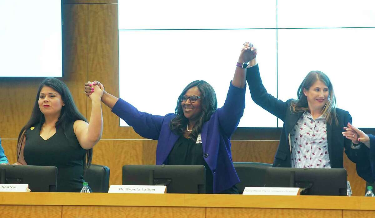 Houston ISD interim superintendent Grenita Lathan, center holds hands with trustee members for a photo Thursday, Jan. 16, 2020 in Houston.
