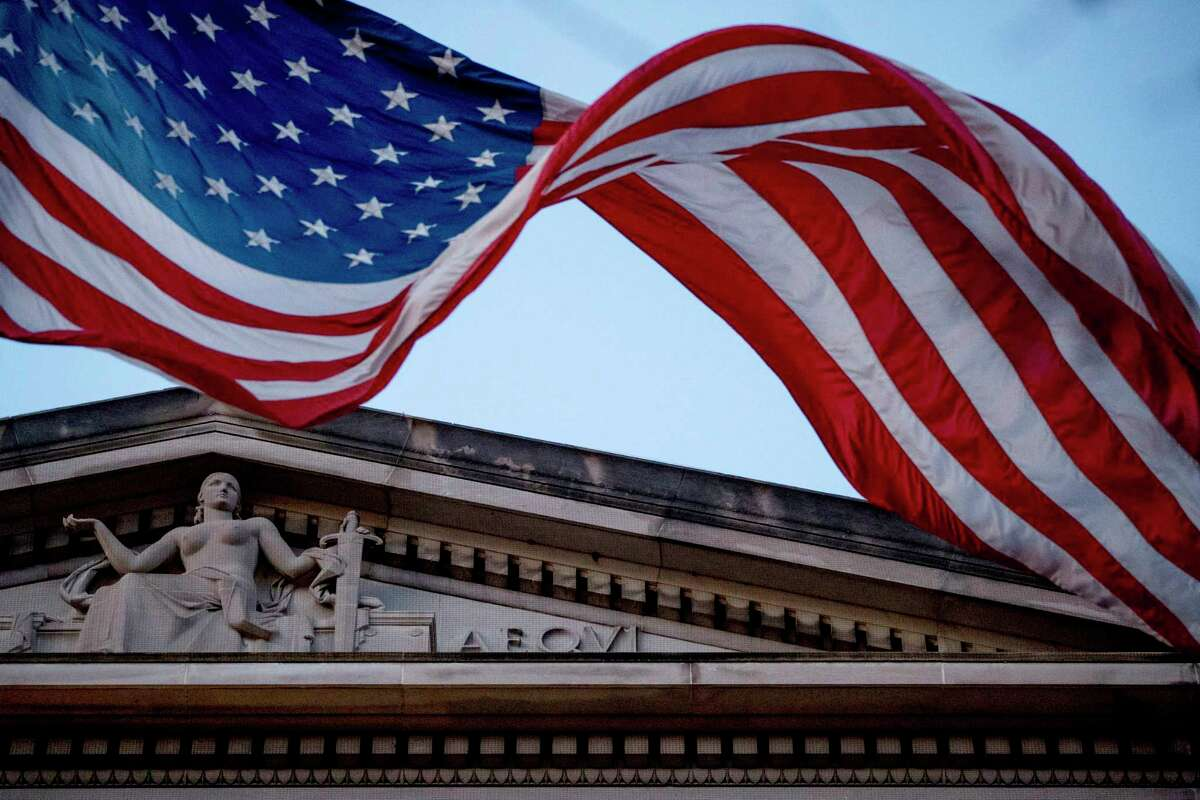 FILE. In this March 22, 2019 file photo, an American flag flies outside the Department of Justice in Washington. (AP Photo/Andrew Harnik)
