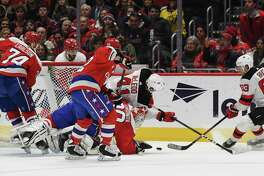 Capitals goaltender Ilya Samsonov (30) makes a save as Devils forward Michael McLeod lands on him during the second period of Thursday night's game between Washington and New Jersey.