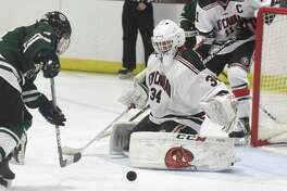 New Canaan goalie Beau Johnson keeps his eyes on the puck as Northwest Catholic's Cam Barone (24) approaches the net during a boys ice hockey game at the Darien Ice House on Saturday, Jan. 11, 2020.