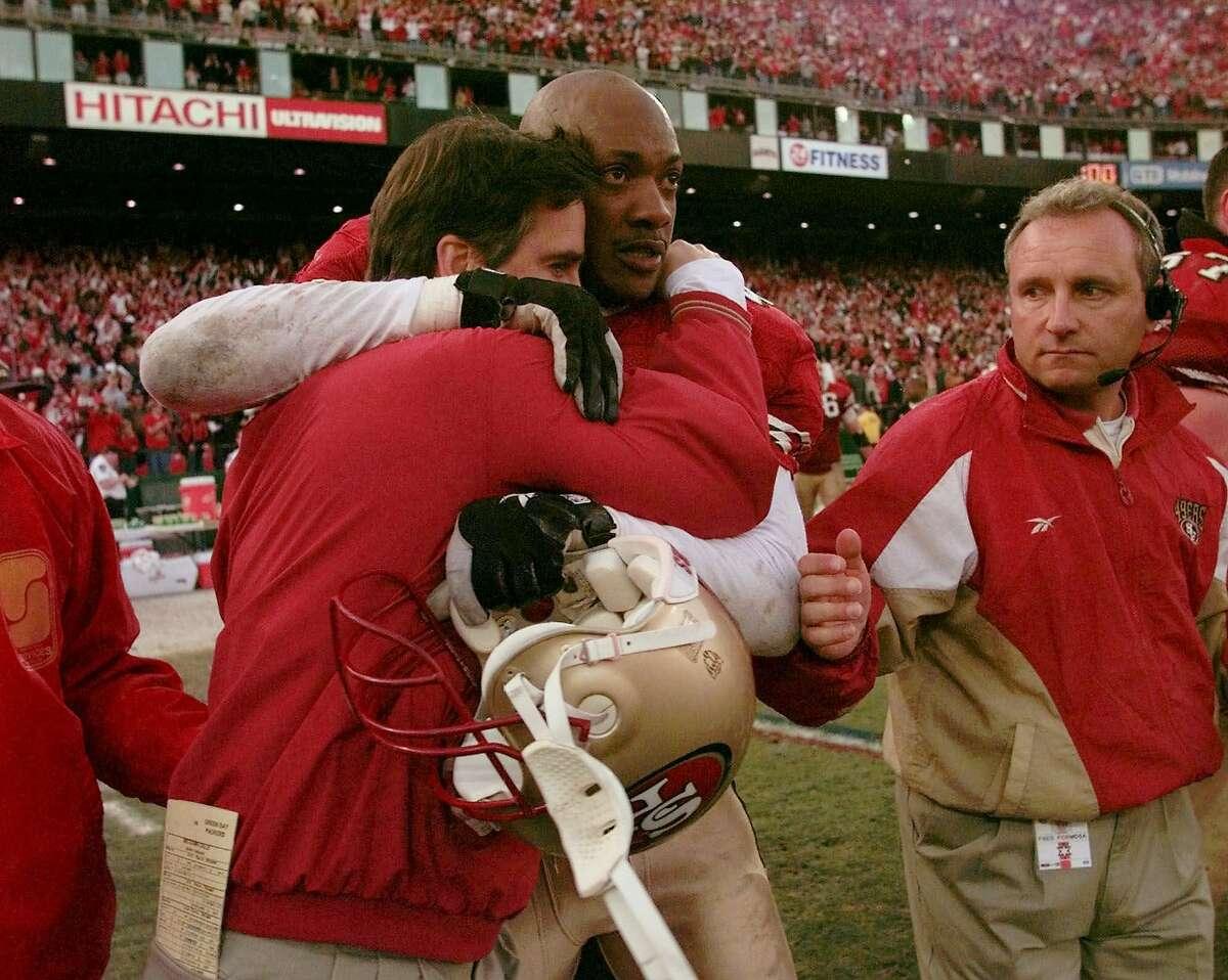 San Francisco 49ers head coach Steve Mariucci, left, hugs Tim McDonald after the Niners beat the Green Bay Packers 30-27 in the NFC wild card playoff game at 3COM Park in San Francisco, Sunday, Jan. 3, 1999. (AP Photo/Paul Sakuma)