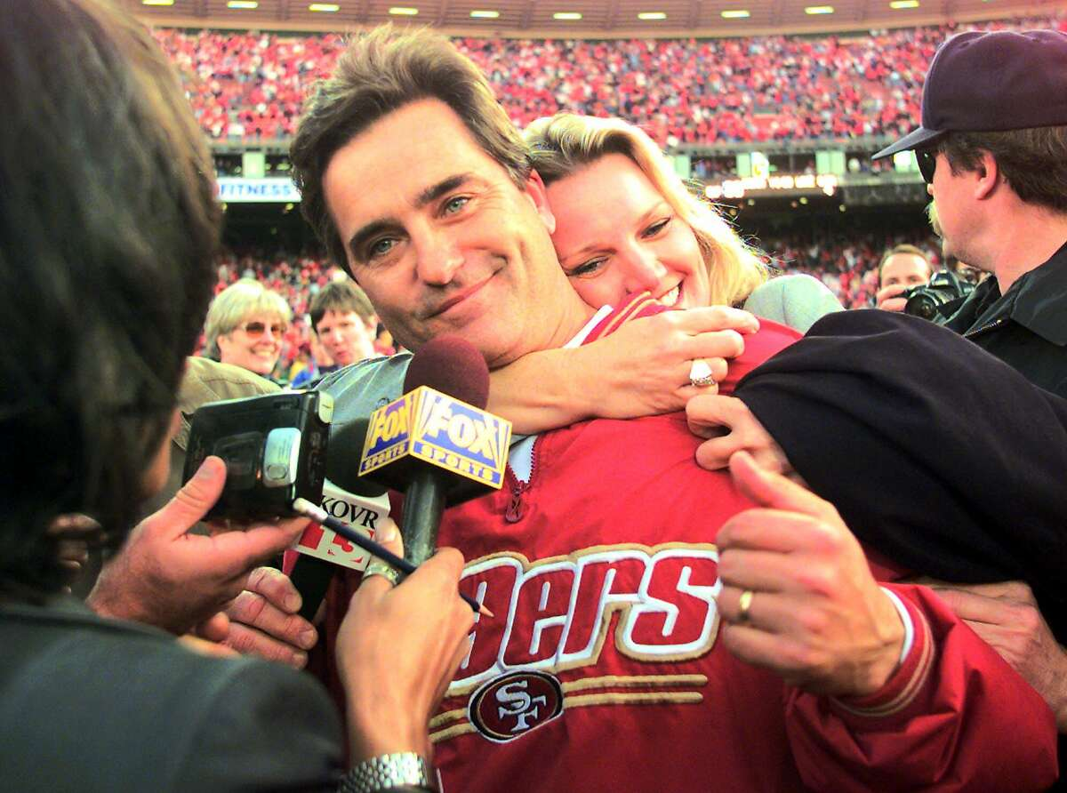 San Francisco 49ers head coach Steve Mariucci is hugged by his wife as he talks with reporters after the Niners beat the Green Bay Packers 30-27 at the NFC wild card playoff game at 3COM Park in San Francisco, Sunday, Jan. 3, 1999. (AP Photo/Susan Ragan)