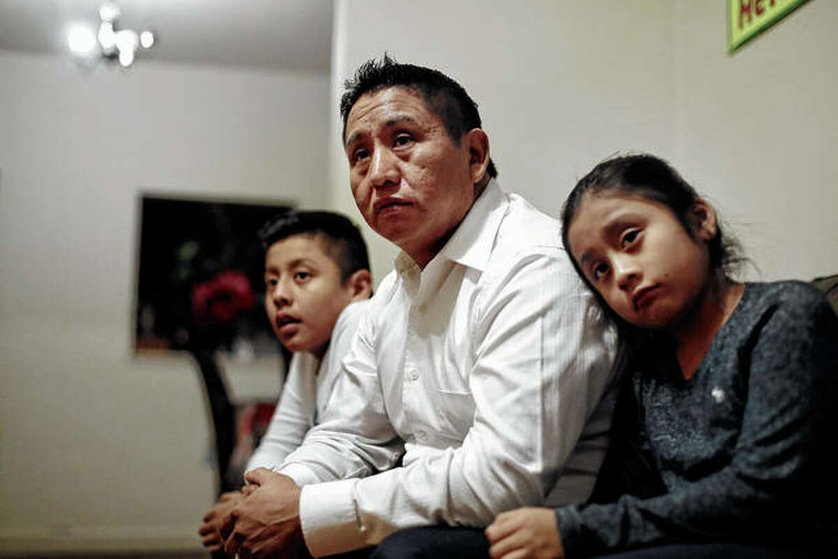 """Audencio Lopez (center), who crossed the border illegally as a teenager in 1997, is seated with two of his children, Anaias (left), 12, and Mercy, 8, at their home in Lynn, Massachusetts. After going through the immigration court process for seven years, Lopez was told at a court hearing this past fall that the government won't oppose granting him a visa because of his """"exemplary"""" record and community service. But Lopez admits the family's joy is tempered by uncertainty because his wife's immigration status remains unresolved."""