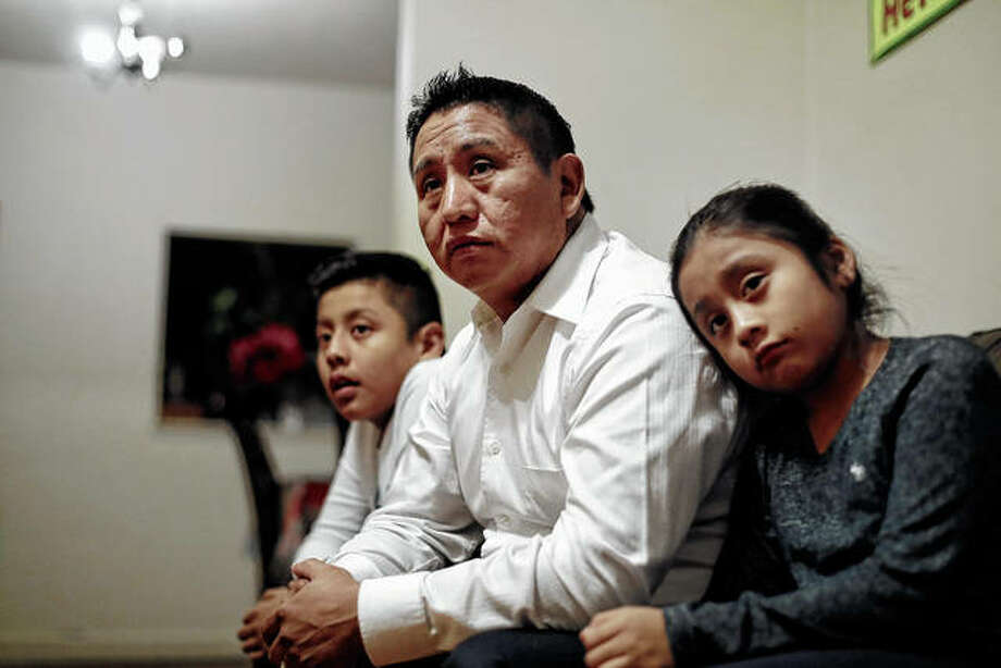 """Audencio Lopez (center), who crossed the border illegally as a teenager in 1997, is seated with two of his children, Anaias (left), 12, and Mercy, 8, at their home in Lynn, Massachusetts. After going through the immigration court process for seven years, Lopez was told at a court hearing this past fall that the government won't oppose granting him a visa because of his """"exemplary"""" record and community service. But Lopez admits the family's joy is tempered by uncertainty because his wife's immigration status remains unresolved. Photo: Steven Senne 