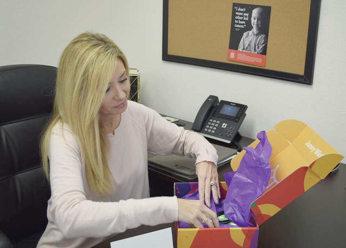 Kimberly Wade puts together a box the Kids Shouldn't Have Cancer Foundation sends to those who support the foundation. She started the foundation in the memory of her son, Jonny, who died from cancer at age 8.