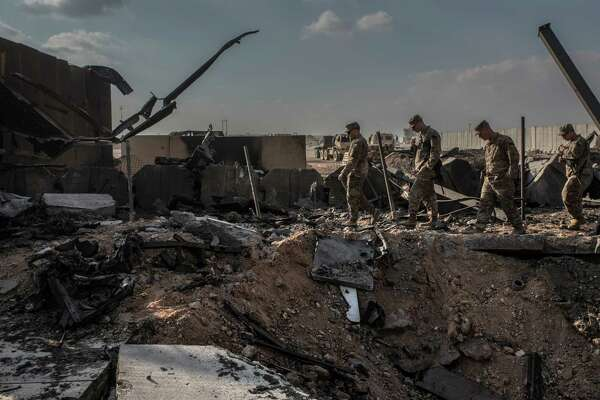 U.S. officials near a crater caused by Iranian airstrikes inside the Ain al-Asad base near Anbar, Iraq, on Jan. 13, 2020.
