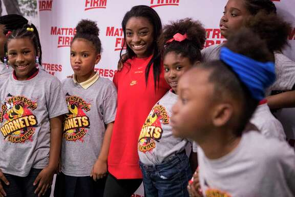 Olympic gold medalist Simone Biles gathers with group of girls for photos after leading them in a set of stretching exercises Thursday, Jan. 16, 2020, at Nathaniel Q. Henderson Elementary School in Houston. During Biles' wellness chat, she spoke to the young ladies about the three pillars of the holistic health triangle - fitness, diet and sleep.