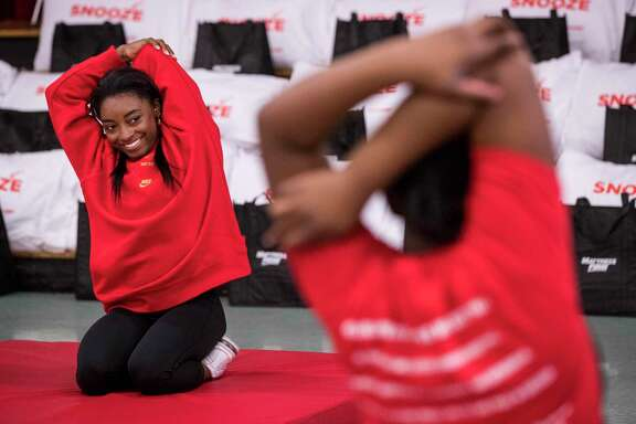 Olympic gold medalist Simone Biles leads stretching exercises with a group of girls Thursday, Jan. 16, 2020, at Nathaniel Q. Henderson Elementary School in Houston. During Biles' wellness chat, she spoke to the young ladies about the three pillars of the holistic health triangle - fitness, diet and sleep.