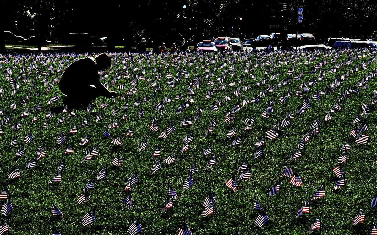 Ryan Conklin straightens flags placed on the Mall by Iraq and Afghanistan Veterans for America, an advocacy group trying to draw awareness to the issue of veteran suicide.