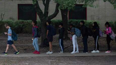 Bellaire High School students going back to school for the first time since Tuesday after 19-year-old senior Cesar Cortez was accidentally shot and killed by a 16-year-old student on campus on Thursday, Jan. 16, 2020, in Bellaire. A long line wrapped around the school building as the students were required to go through one door and have their bags checked.