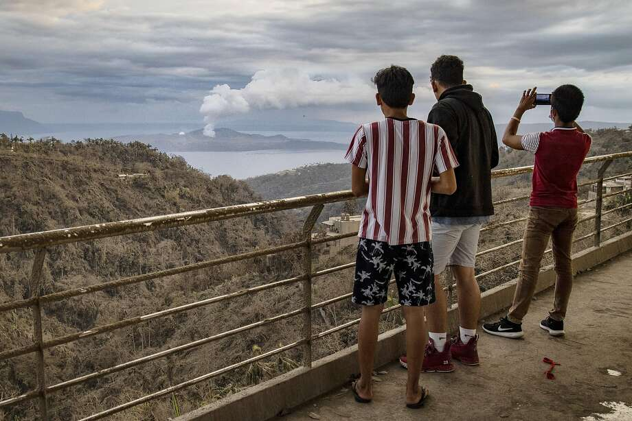 Residents take photographs as the Taal volcano spews ash near the town of Tagaytay in Cavite province, Philippines. Photo: Ezra Acayan / Getty Images