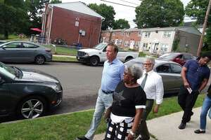 Then-Democratic gubernatorial nominee Ned Lamont takes a tour of the Second Stoneridge co-op with state Sen. Marylin Moore and Bridgeport resident Max Medina on June 5, 2018.