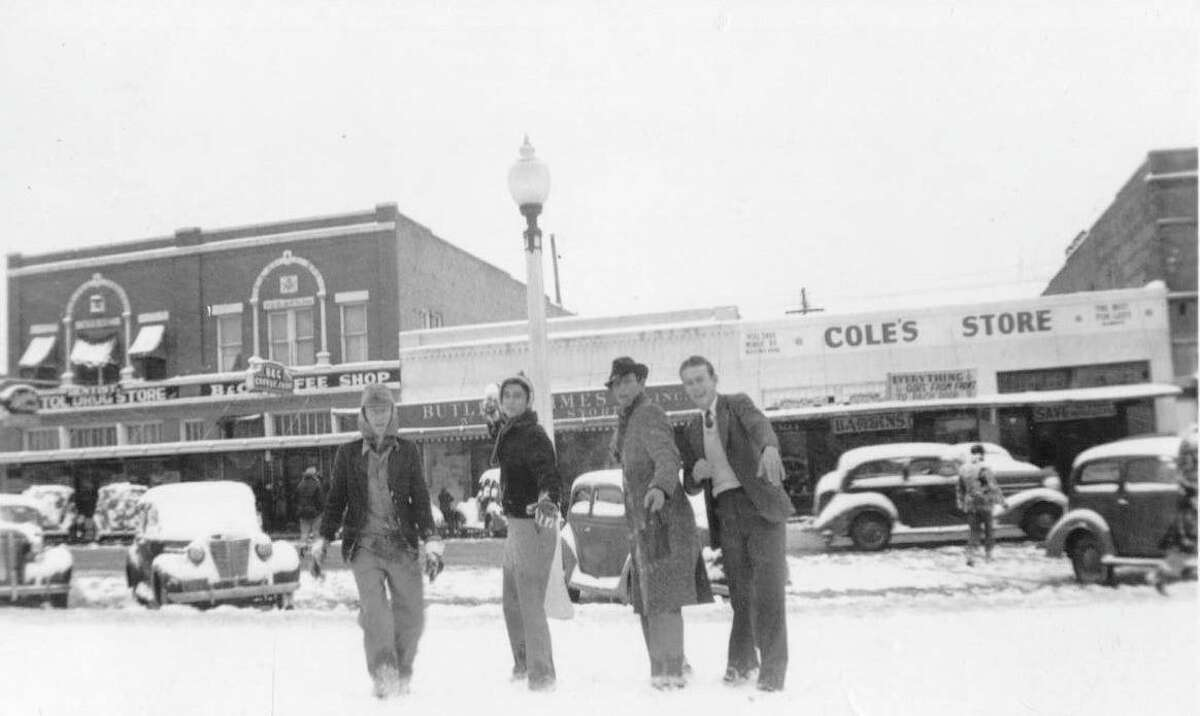 Four men engage in a snowball fight on the courthouse square this week in January 1940.