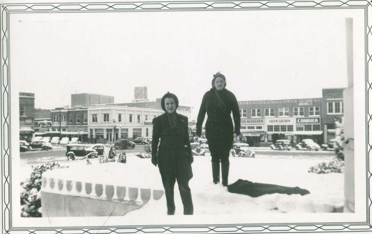 Two ladies on the Montgomery County Courthouse Square after a rare snow blanketed Conroe in January 1940.
