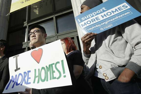 Men hold up signs at a rally outside of City Hall in Oakland, Calif., Tuesday, Jan. 7, 2020. California Sen. Scott Wiener announced amendments to a closely-watched bill that would allow more housing to be built near public transportation. (AP Photo/Jeff Chiu)