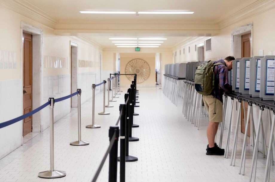 A man stands alone in a row of poll booths as he casts his vote at San Francisco City Hall last year. Photo: File Photo / ONLINE_YES