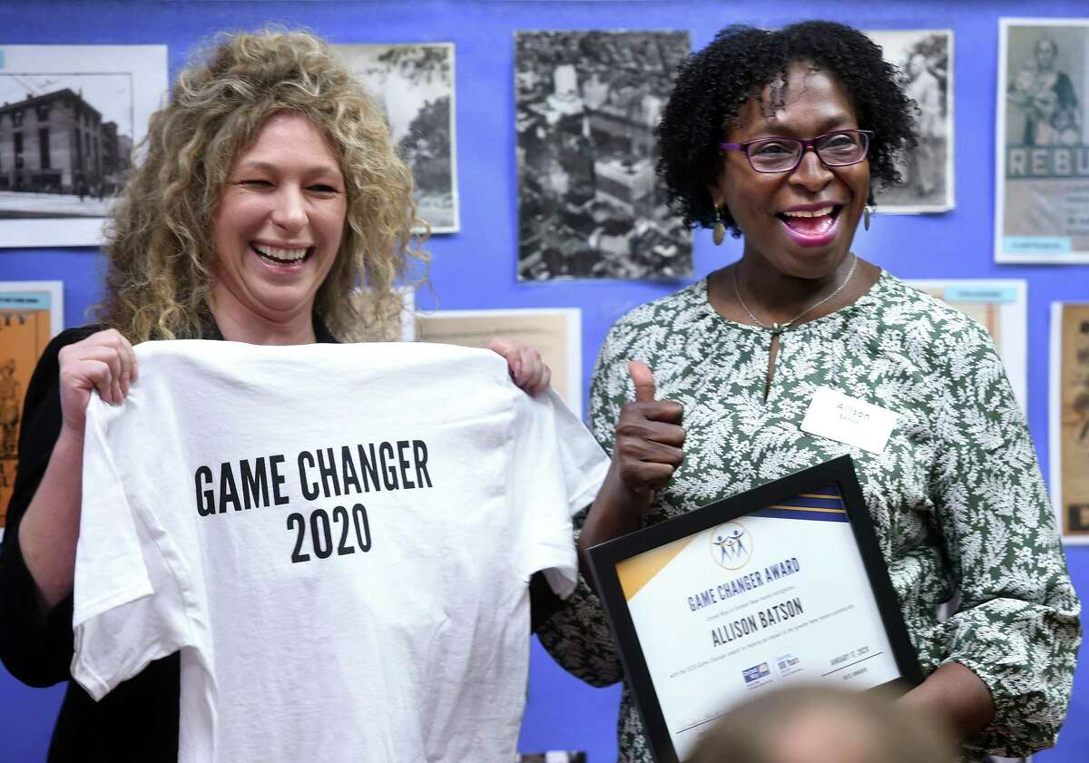 Nicole Grant, left, executive director of the Avangrid Foundation, awards Allison Batson of Hamden the first of 100 Game Changer Awards from the United Way of Greater New Haven on Jan. 17, 2020, for her work in the community. Batson founded the Dinner for a Dollar program at Grace and St. Peter's Church in Hamden, helped organize Abraham's Tent, serves on the board of Columbus House and teaches preschool at Helen Street School in Hamden.