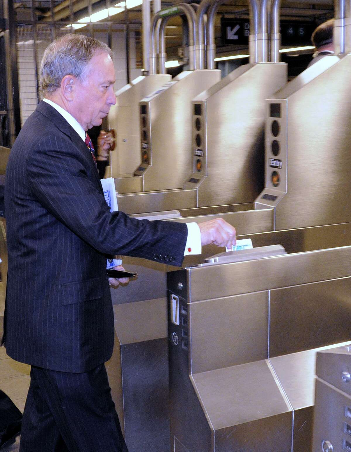 FILE - New York city Mayor Michael Bloomberg swipes into the NYC subway in 2009.