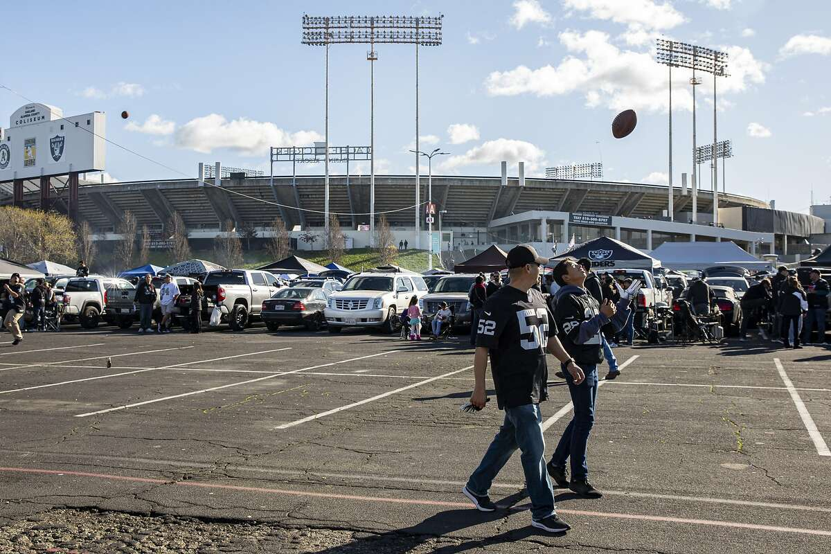 Armando Ochoa and his son Aaron Ochoa, 13, play with the football outside the Oakland Coliseum before the NFL game between the Oakland Raiders and Jacksonville Jaguars on Sunday, Dec. 15, 2019, in Oakland, Calif.