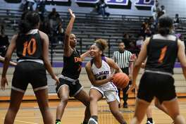 Humble freshman Kameryn Phillips (14) drives to the hoop between a trio of Dobie defenders during the first quarter of their district matchup at Humble High School on Dec. 17, 2019.