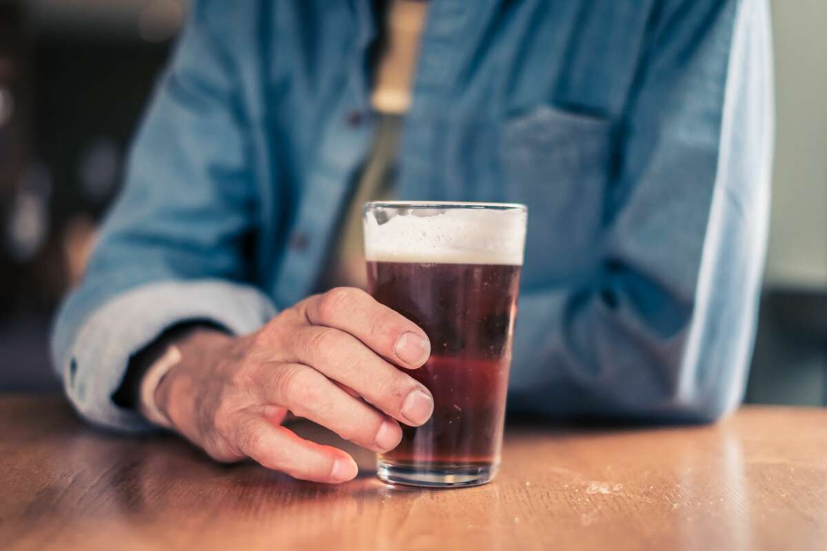 Mid-shot of a man holding an half-pint of beer or real ale, leaning on a table on a Saturday afternoon in an English pub.