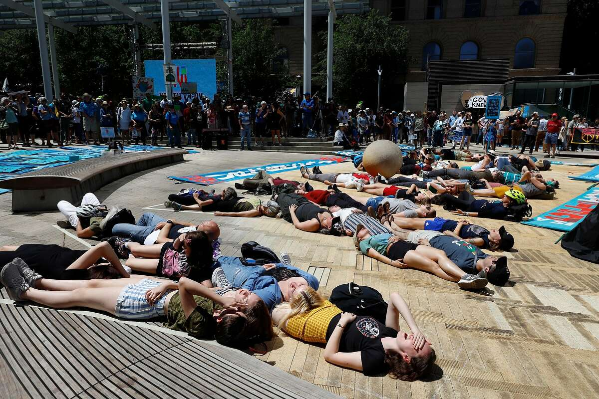 Supporters spell out a message with their bodies at a rally Tuesday, June 4, 2019 for a group of young people who filed a lawsuit saying U.S. energy policies are causing climate change and hurting their future. The group faces a major hurdle Tuesday as lawyers for the Trump administration argue to stop the case from moving forward. in Portland, Ore.