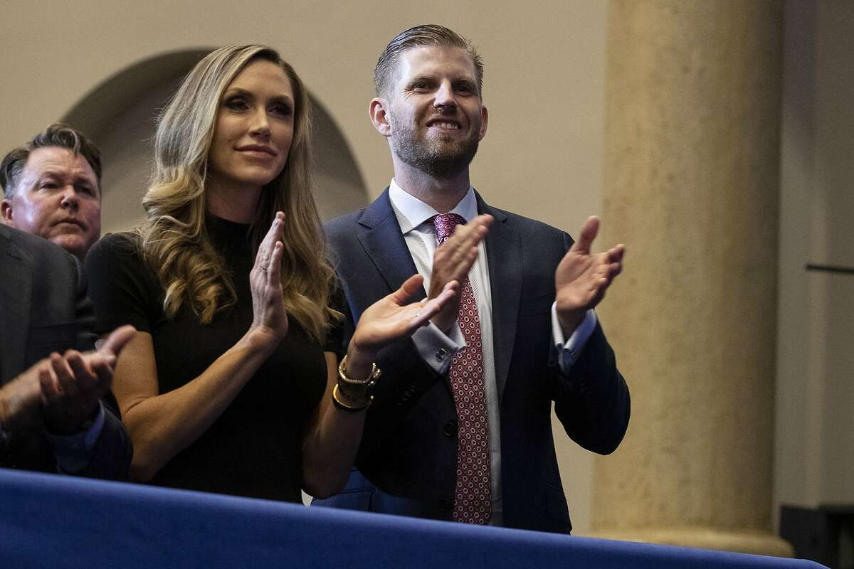 """Eric Trump, the son of President Donald Trump, and Lara Trump listen as President Donald Trump speaks during an """"Evangelicals for Trump Coalition Launch"""" at King Jesus International Ministry, Friday, Jan. 3, 2020, in Miami. (AP Photo/ Evan Vucci)"""