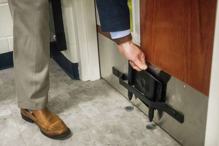 Craig Carmoney, superintendent for Meridian Public School District, demonstrates how a metal security boot is used on a classroom door Tuesday at Meridian Elementary. (Katy Kildee/kkildee@mdn.net)