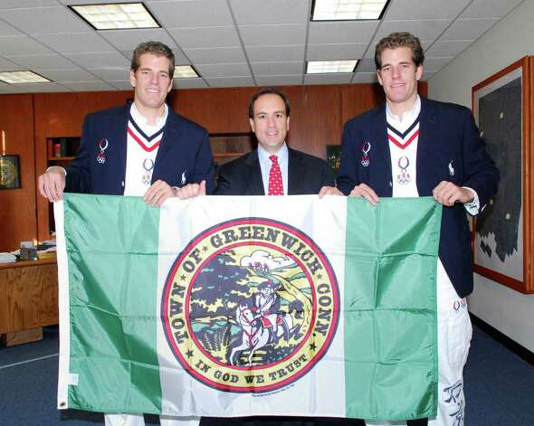 Tyler Winklevoss, left, and his twin brother, Cameron Winklevoss, right, pose with Greenwich First Selectman Peter Tesei, holding the flag of Greenwich in 2008 at Town Hall. Photo: File Photo / Greenwich Time File Photo