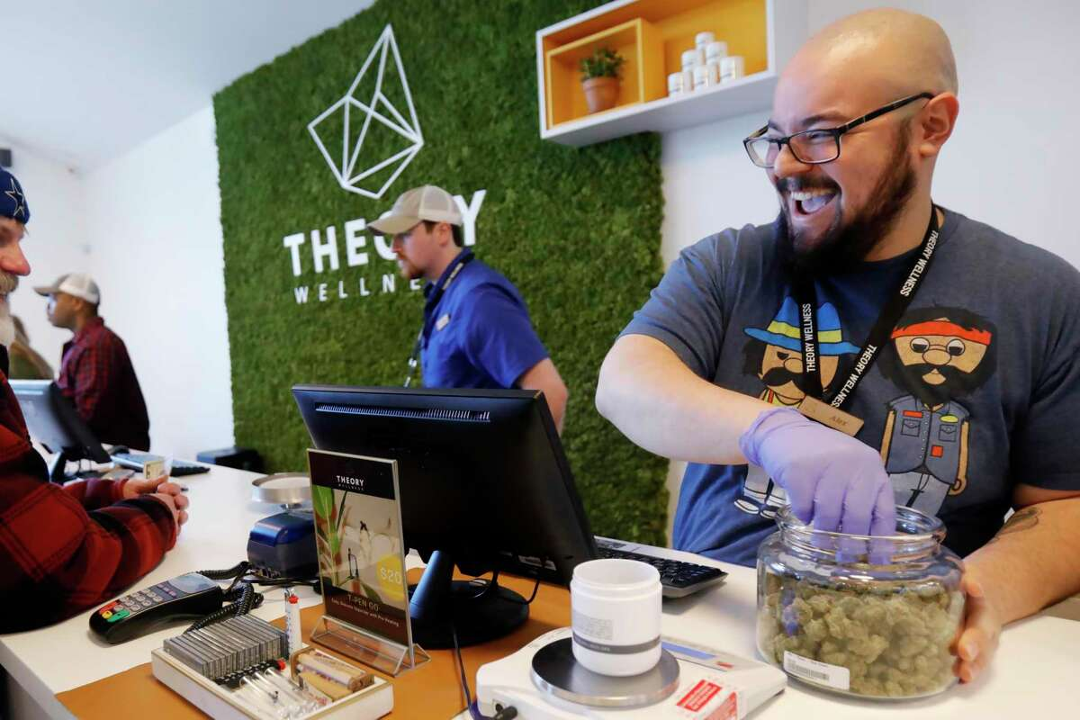 Alex Premoli makes the first sale to a customer on the opening day of recreational marijuana sales at Theory Wellness in Great Barrington, Mass., Friday, January 11, 2019. Theory is the first dispensary in the Berkshires to open its doors for recreational marijuana sales and the opening makes Theory the 6th dispensary of its kind in the state. (Stephanie Zollshan/The Berkshire Eagle via AP)