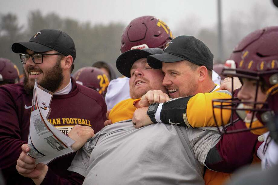 Sheehan Titans head coach John Ferrazzi hugs Pat Miller from behind as the final seconds expire in the 2019 CIAC Class S Football State final. Photo: David G. Whitham / For Hearst Connecticut Media / Stamford Advocate Freelance