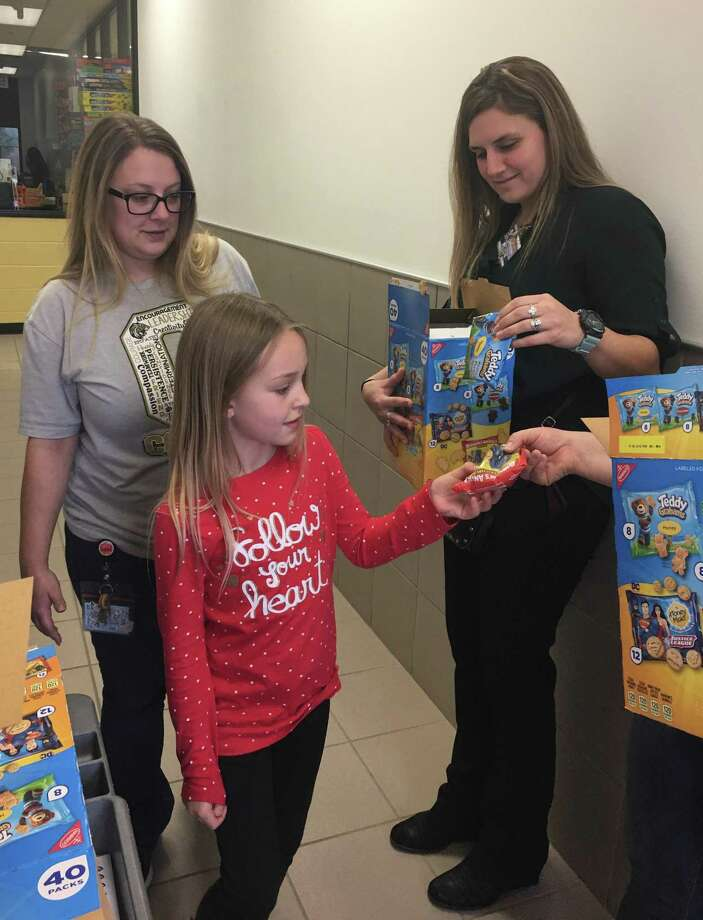 Conroe Noon Lions Club member Amanda Anders (right) helps hand out treats to Bee Club students at the club's adopted school, Reaves Elementary. The club sponsors the incentive program for students with excellent conduct, attendance and grades through a 9-week grading program. Photo: Courtesy Photo