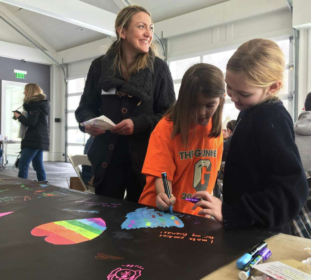 Neely Gritti, center, and Audrey Psomas, right, paint a mural at the inaugural Washington Gives event at the Judy Black Memorial Park and Gardens in Washington, Conn. The event commemorates Martin Luther King Jr. Day with service projects.